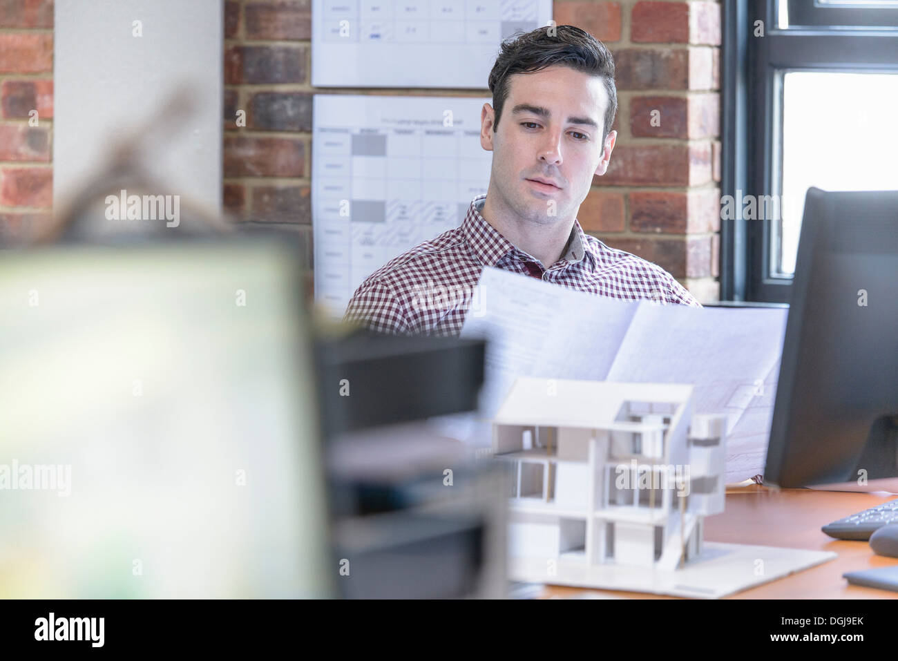 Architect inspecting plans at desk with model building - Stock Image