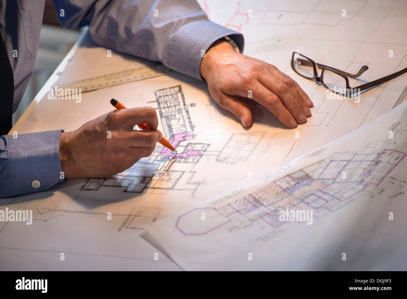 Architect drawing plans at drawing board, close up - Stock Image