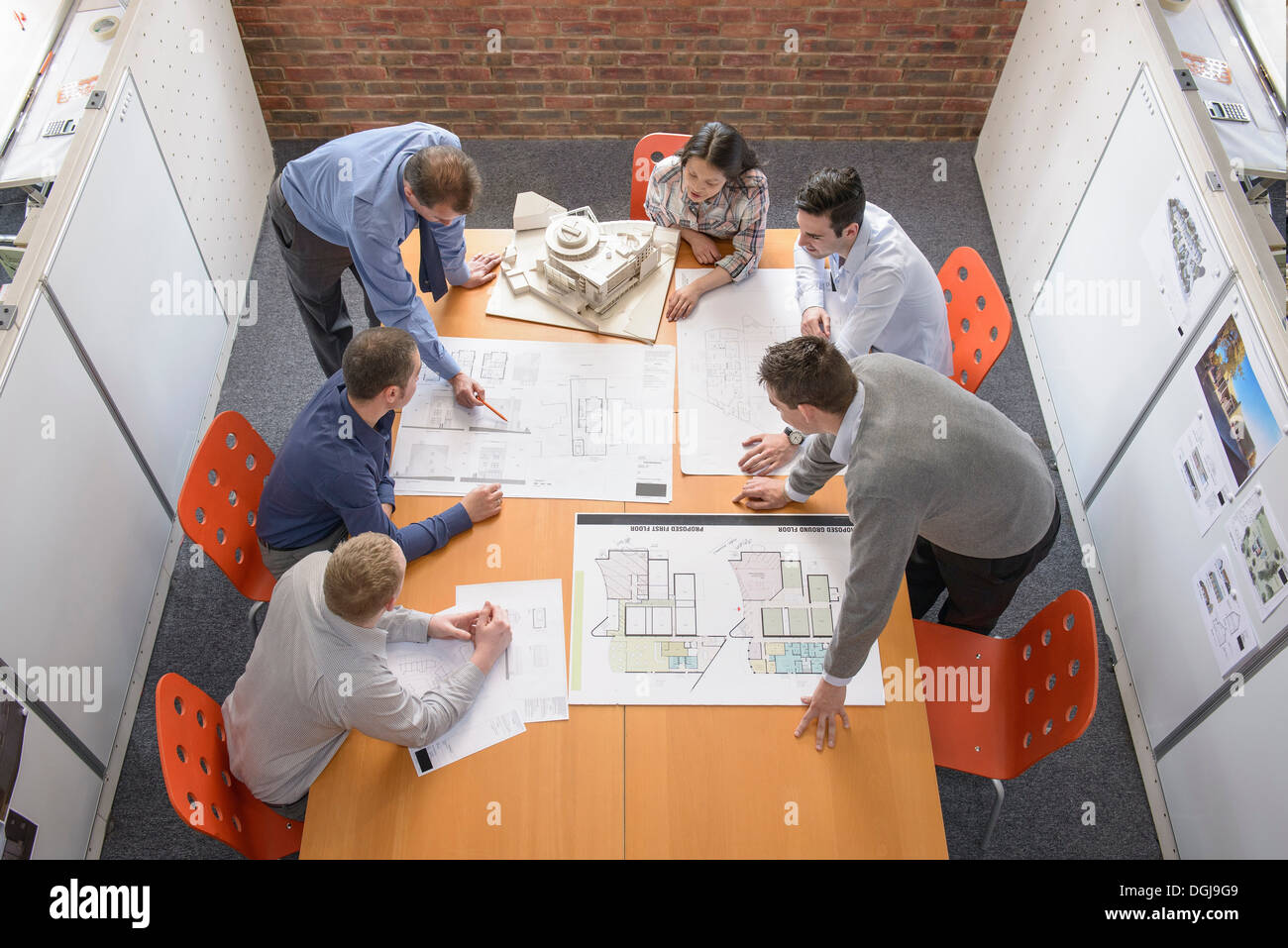 Team of architects discussing plans in meeting room - Stock Image