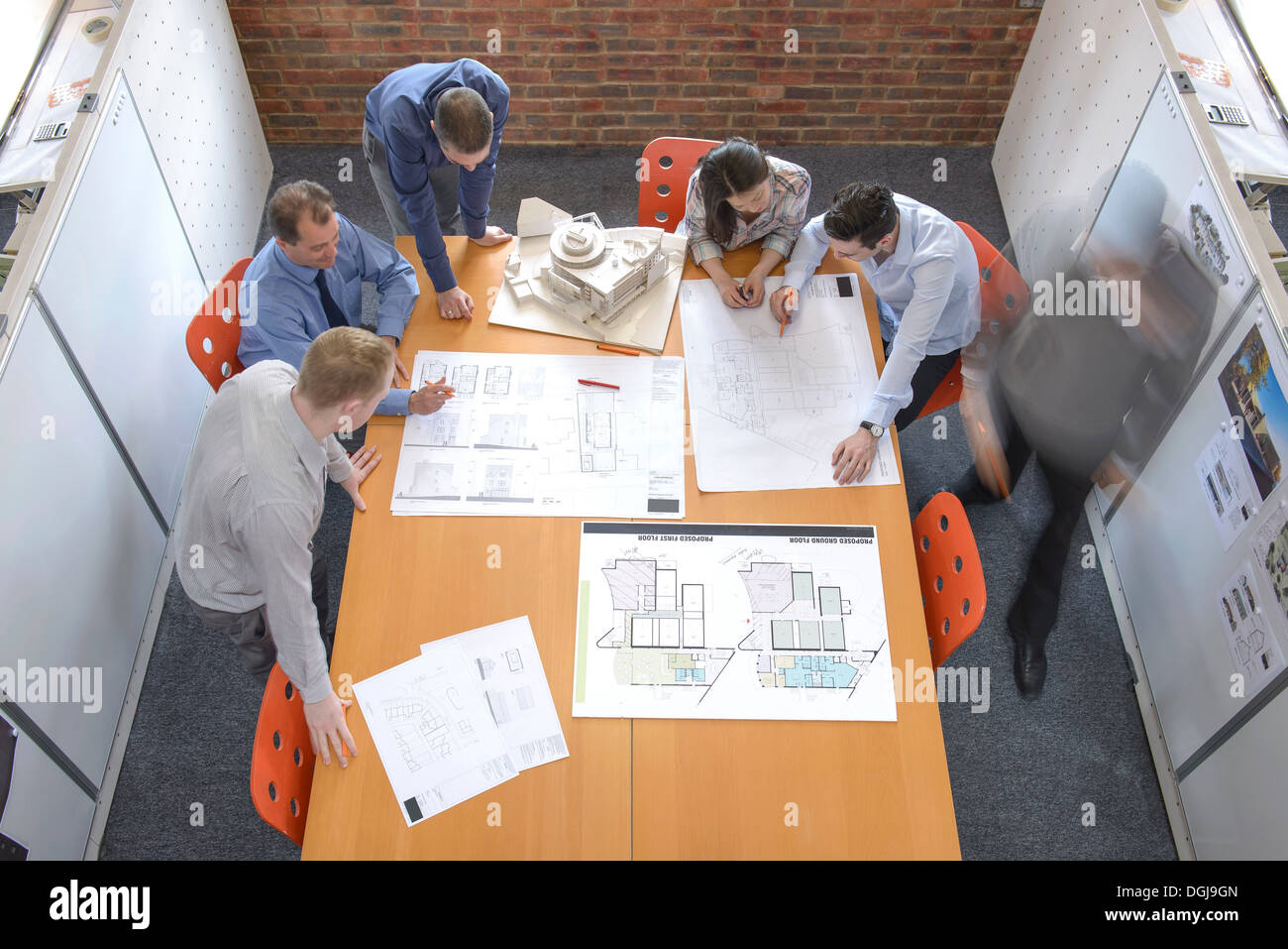 Team of architects discussing plans in meeting room, blurred motion - Stock Image