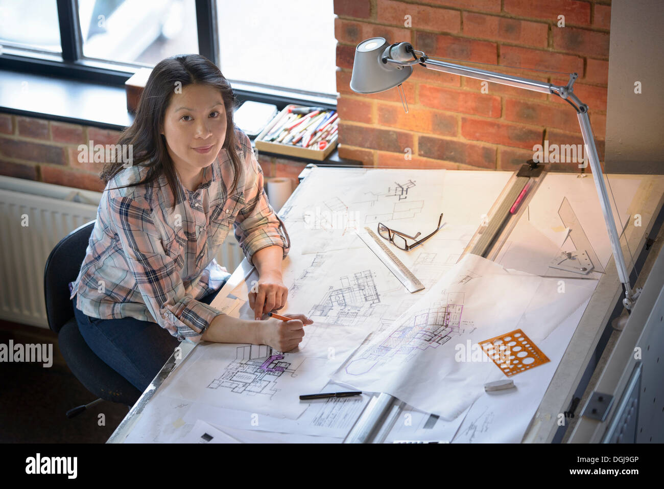Architect drawing plans at drawing board, portrait - Stock Image