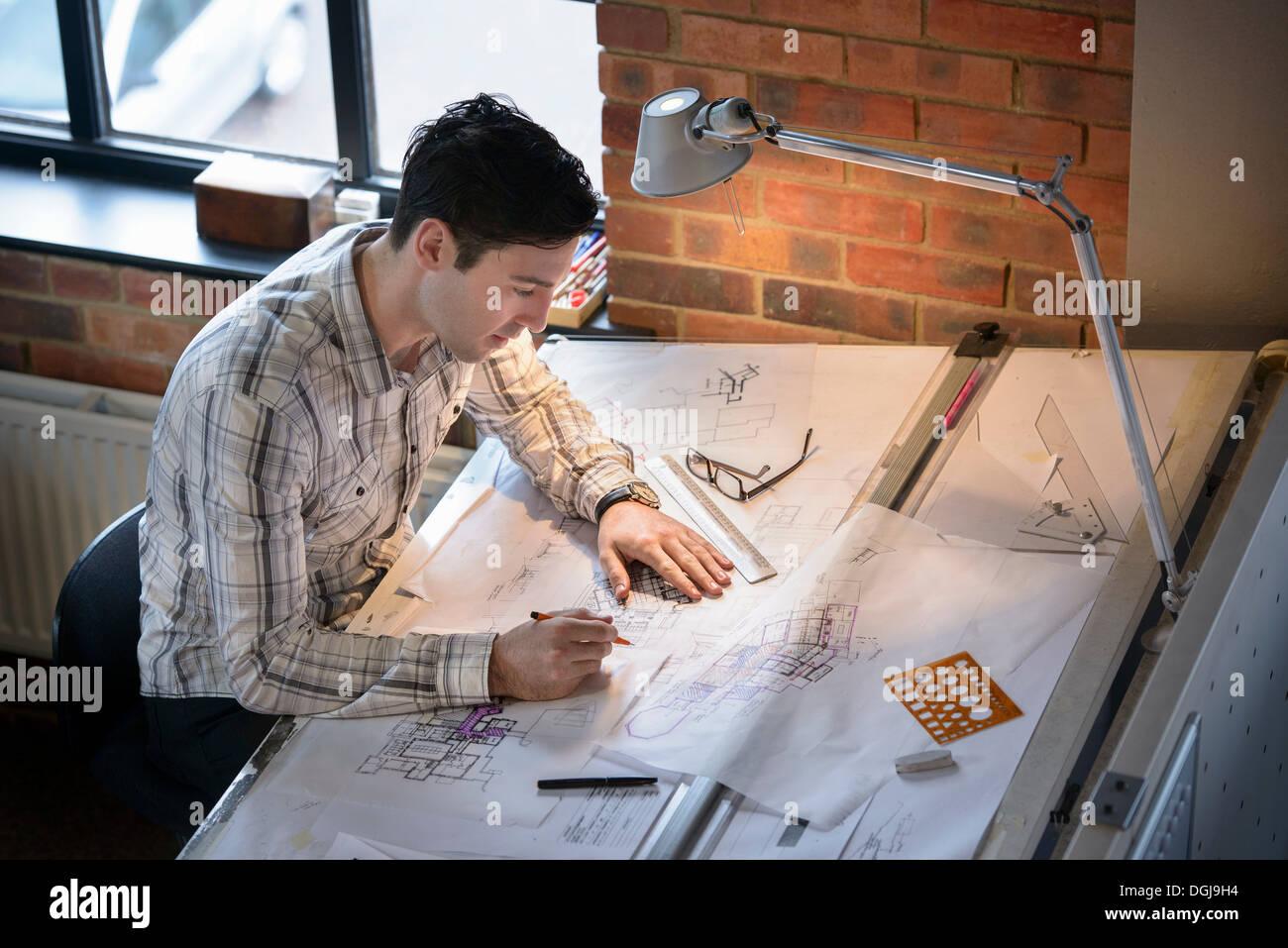 Architect drawing plans at drawing board - Stock Image