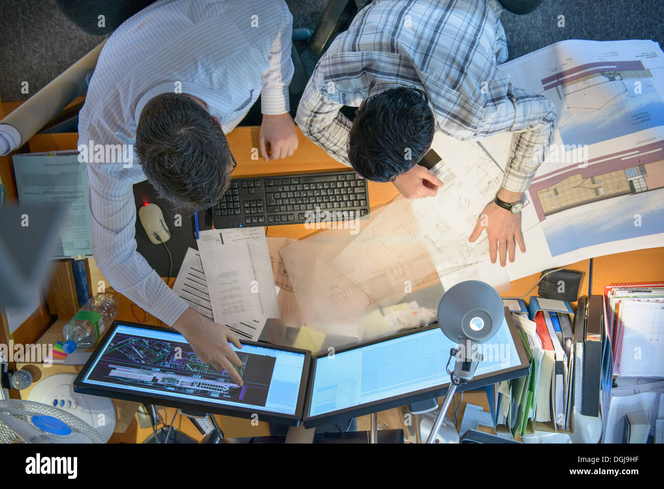 Architects working together on plans and screens at desk - Stock Image