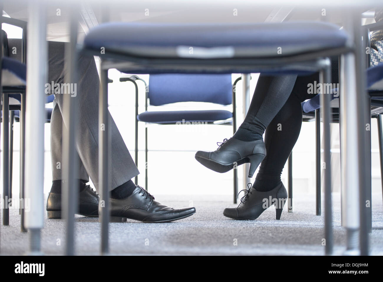 Businessman and woman in meeting, low section - Stock Image