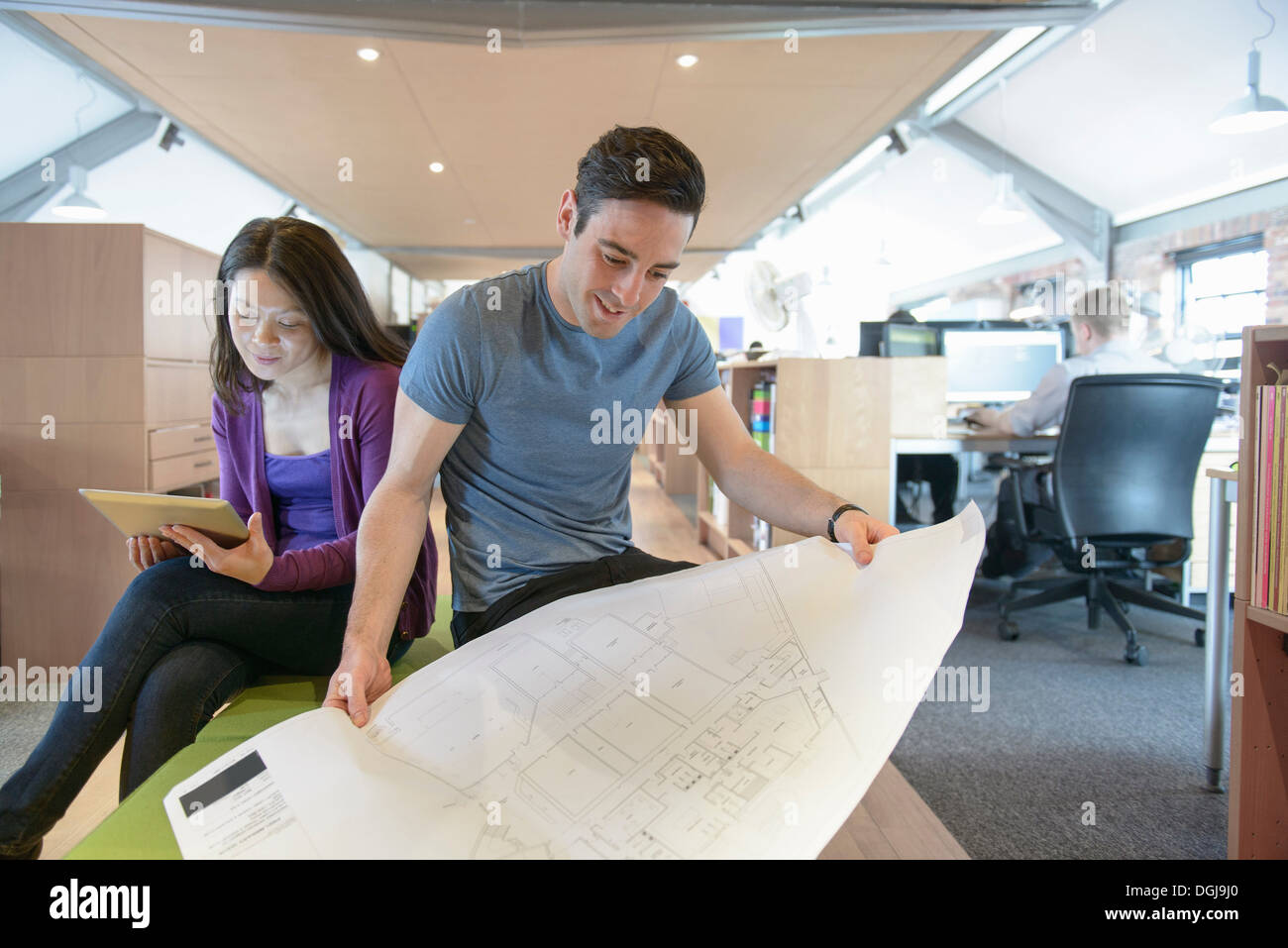 Business colleagues looking at plans in modern office - Stock Image