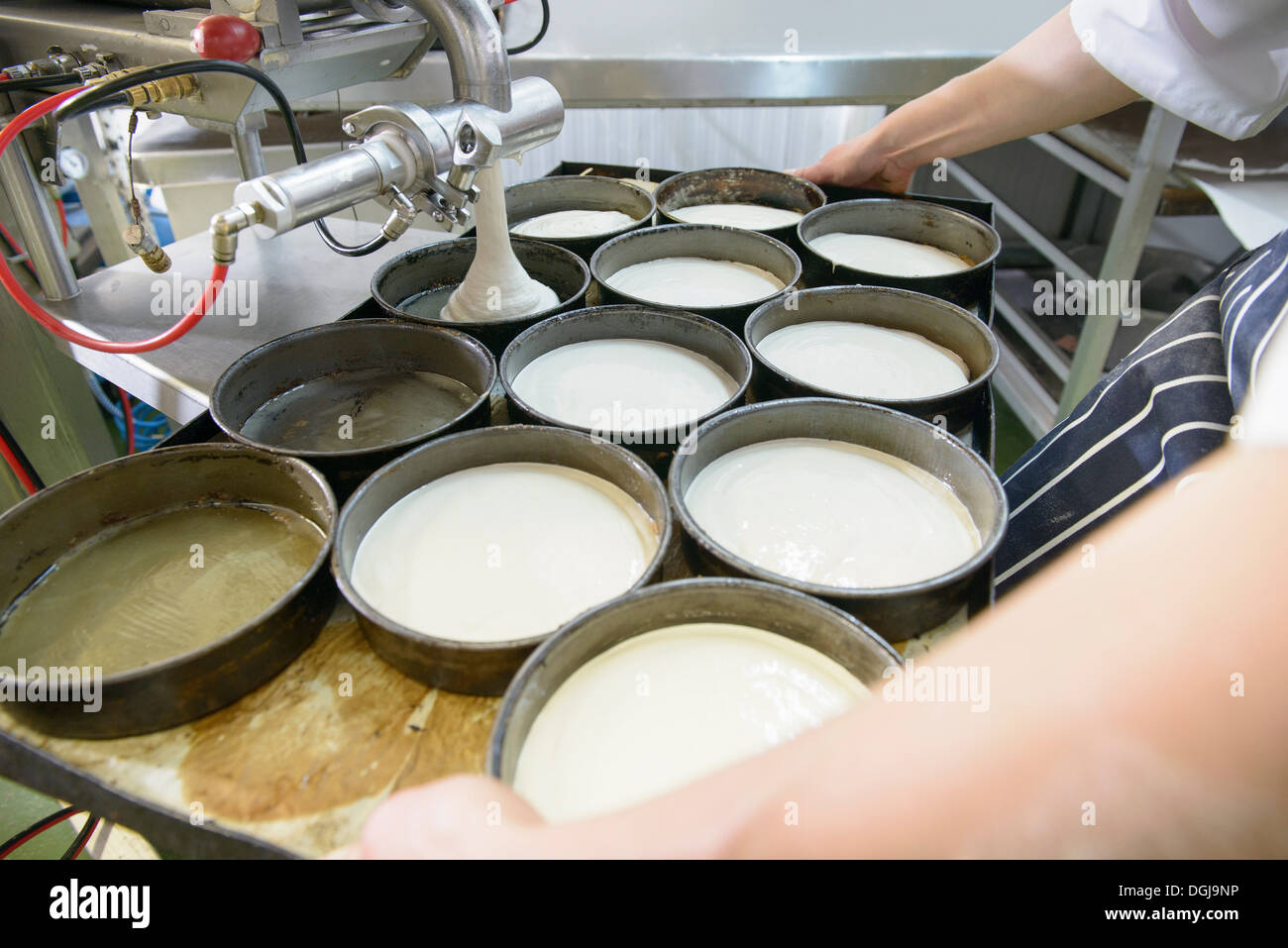 Baker measuring out dough in dishes, close up - Stock Image