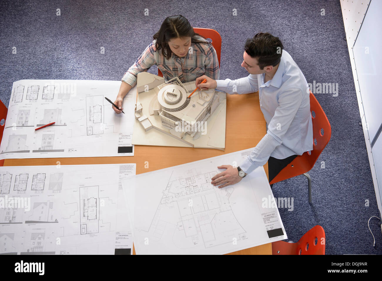 Two architects discussing plans and scale model building in meeting room - Stock Image