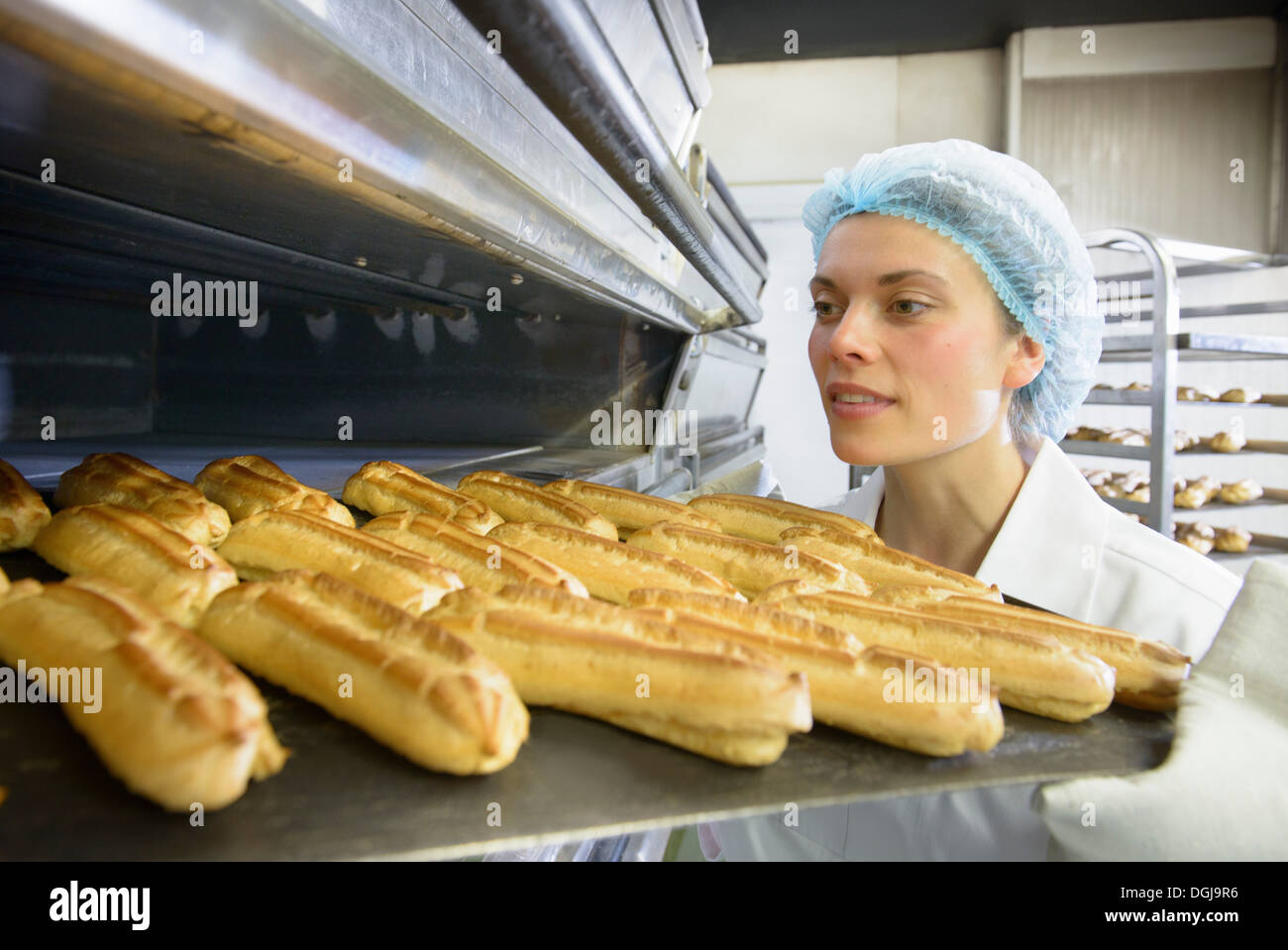 Baker removing tray of baked pastries from oven in bakery - Stock Image