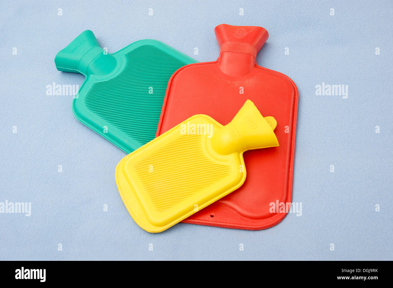 3 hot water bottles including a child's size one - Stock Image