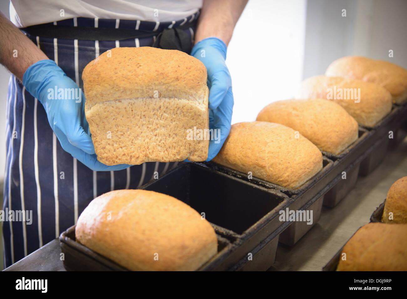 Baker holding loaf of freshly baked bread Stock Photo