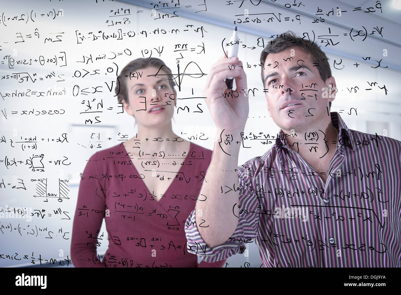 Mathematicians writing complex scientific equations on screen - Stock Image