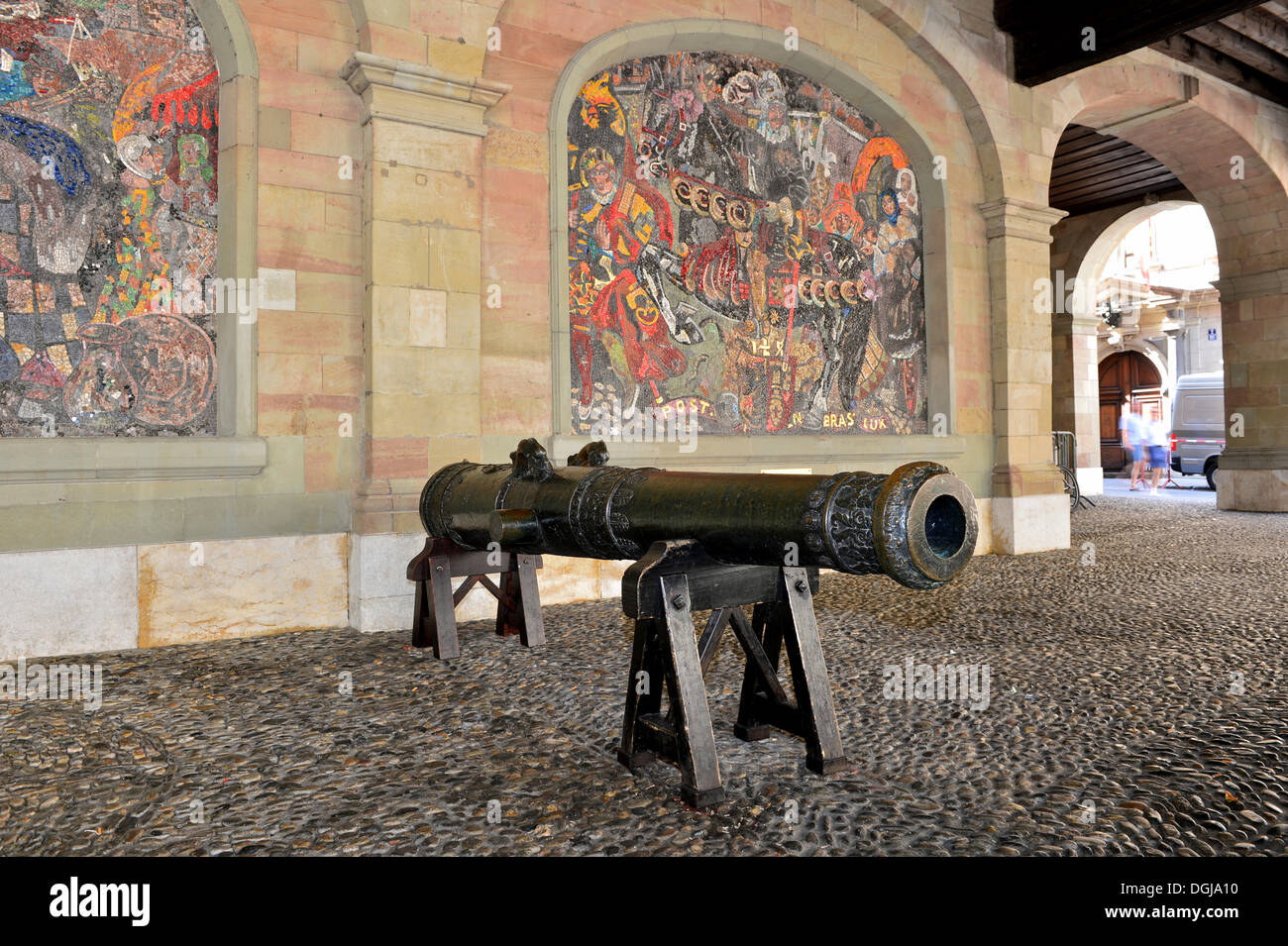 Medieval cannon of the Geneva artillery in the former armoury, in front of a mosaic by Alexandre Cingria depicting Huguenot - Stock Image