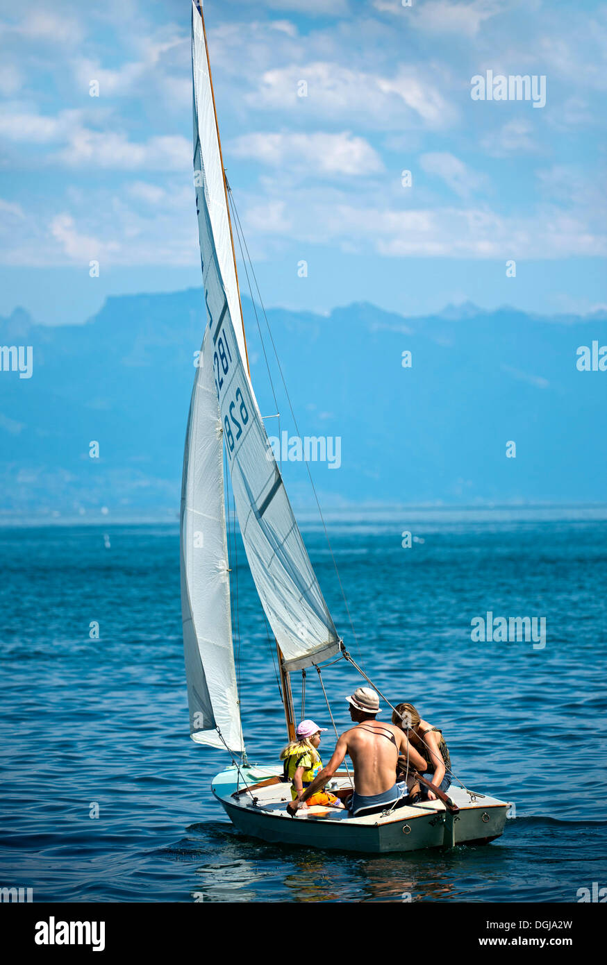 Family trip on a sail boat on Lake Geneva near Morges, Vaud Alps at back, Alpes vaudoises, Canton of Vaud, Switzerland, Europe - Stock Image