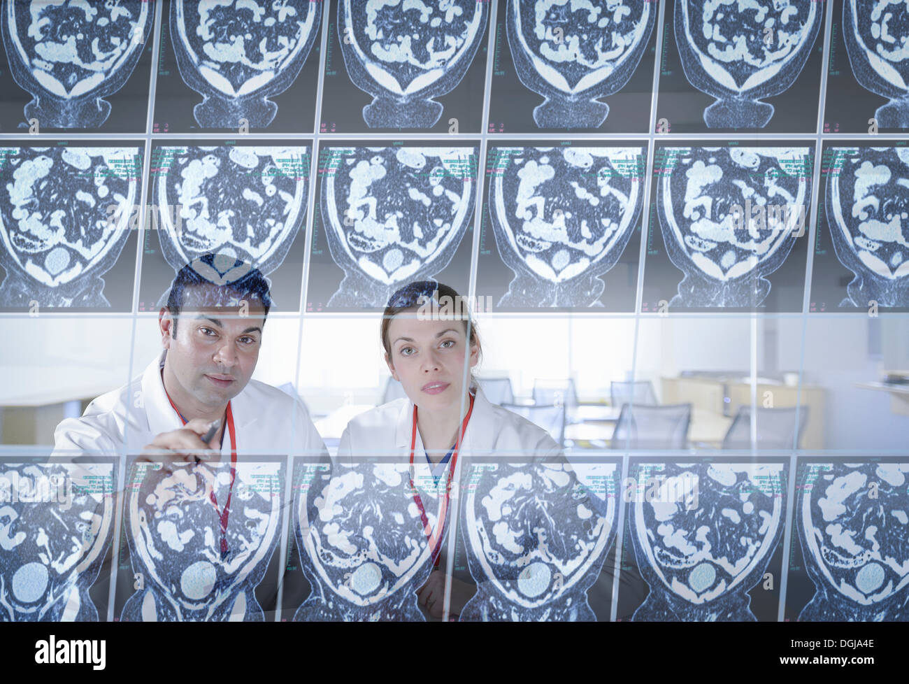 Surgeons inspecting computed tomography (CT) scans on screen Stock Photo