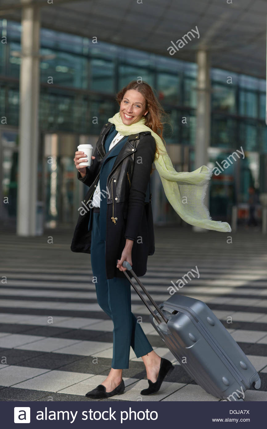 Young woman at airport with wheeled case and coffee - Stock Image