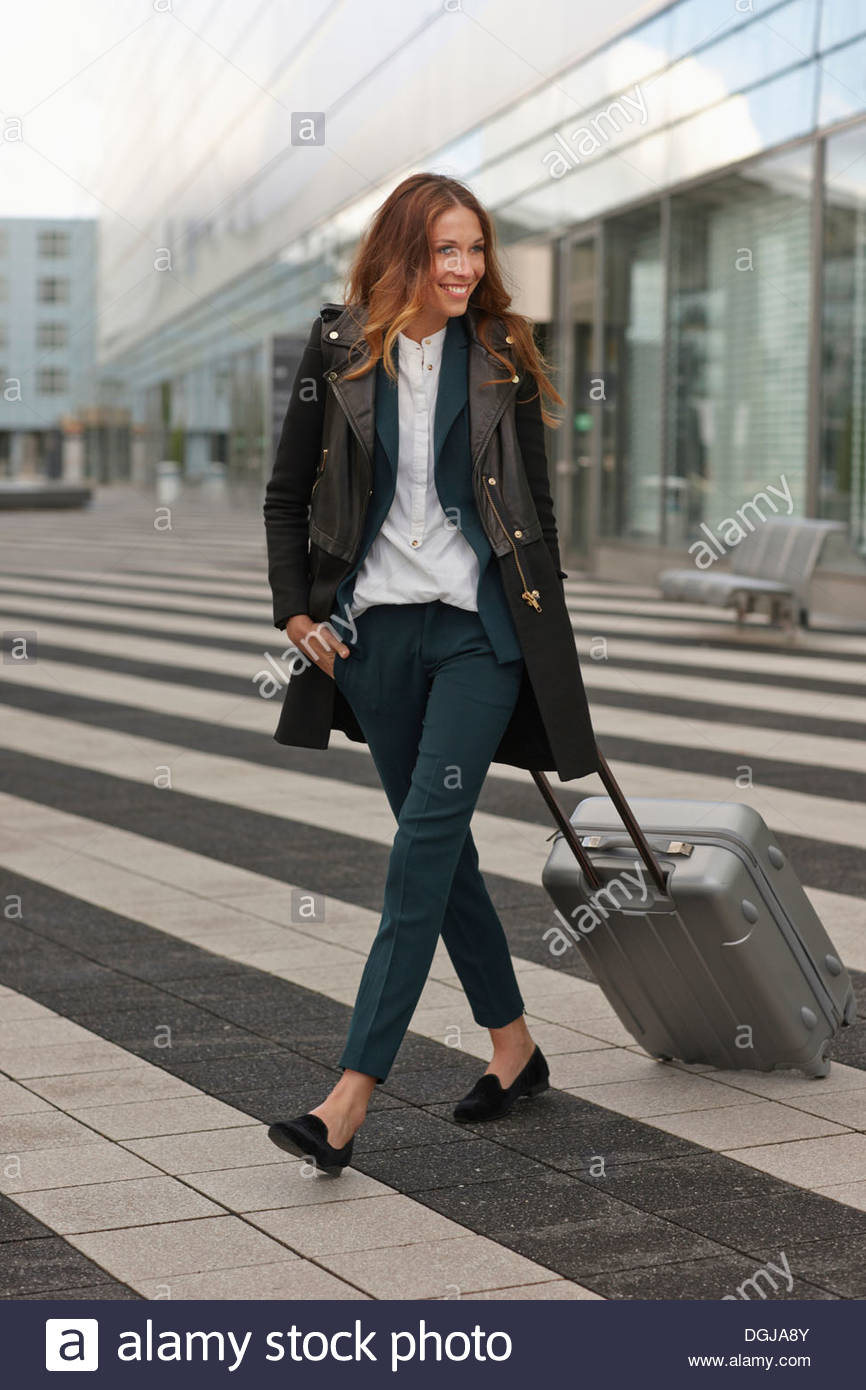 Young woman outside airport with trolley case - Stock Image