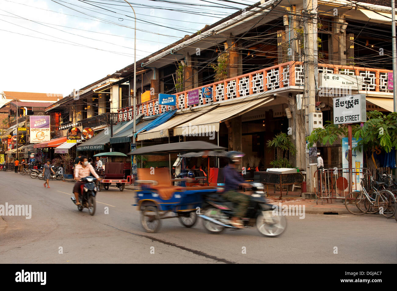 Rickshaw in traffic in front of restaurants and bars in Pub Street, Siem Reap, Siem Reap Province, Cambodia - Stock Image