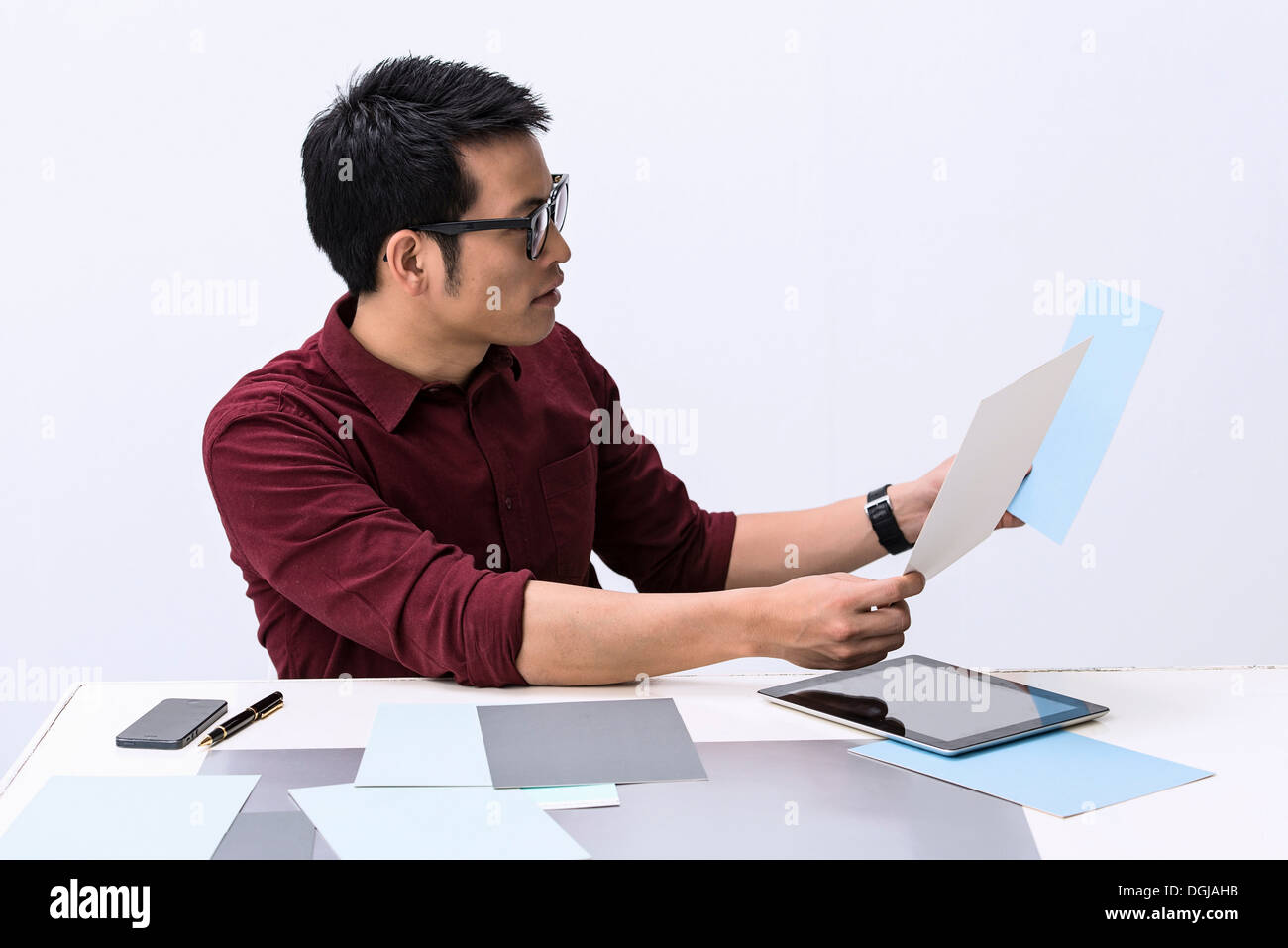 Young male designer looking at color swatch samples - Stock Image