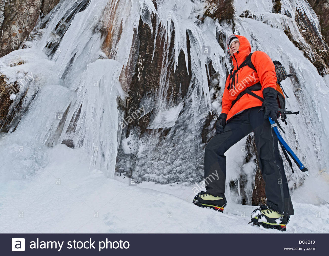 Female climber in front of frozen waterfall, Tryfan, Ogwen Valley, Snowdonia - Stock Image