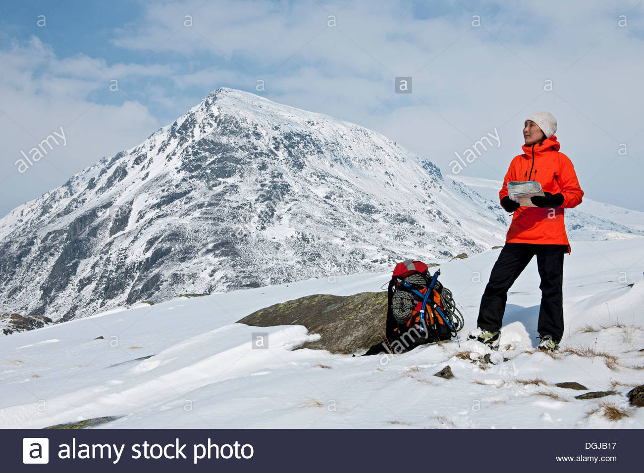 Female climber with map on snow covered mountain, Carneddau, Snowdonia Stock Photo