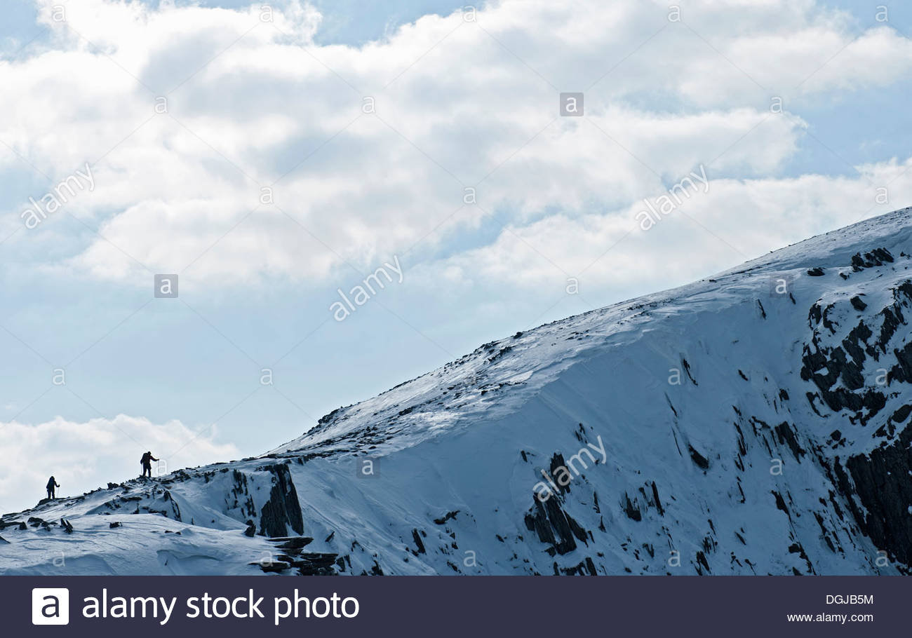 Two climbers silhouetted along snow covered ridge, Castell y Geifr, Snowdonia - Stock Image