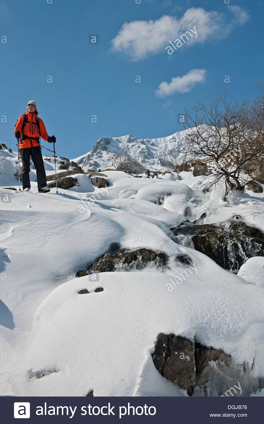 Female climber walking down snow covered mountain, Pen y Benglog, Snowdonia - Stock Image