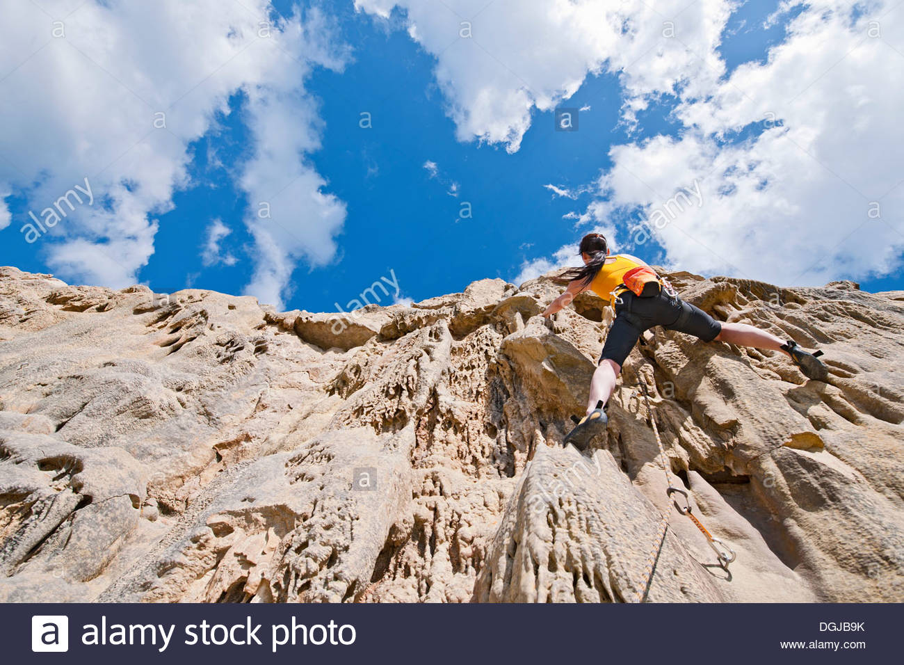 Female rock climber nearing cliff top - Stock Image