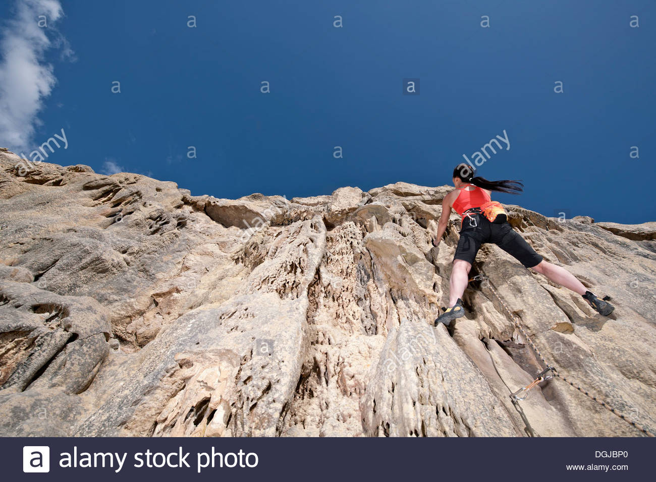 Female rock climber nearing cliff top Stock Photo