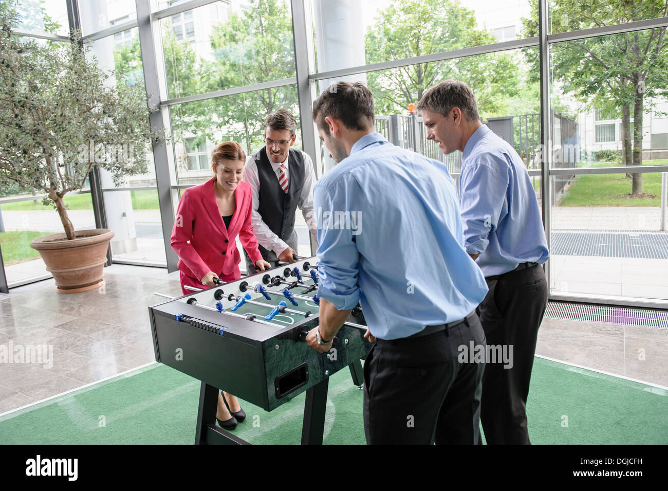 Businesspeople playing table football in lobby - Stock Image