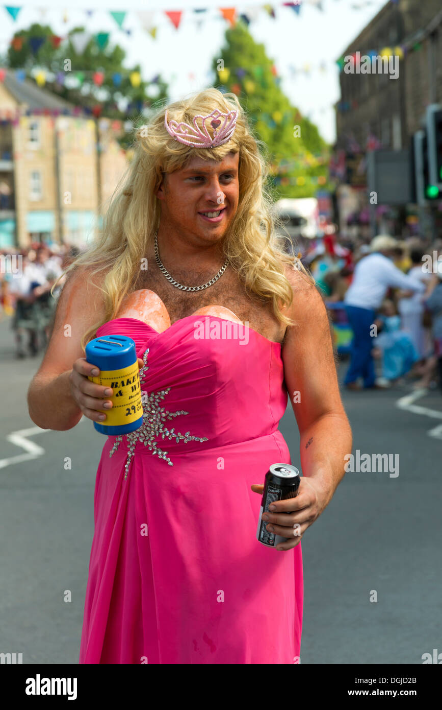 Man wearing a wig and pink dress Bakewell carnival  parade an annual charity raising event  Peak District Derbyshire Stock Photo