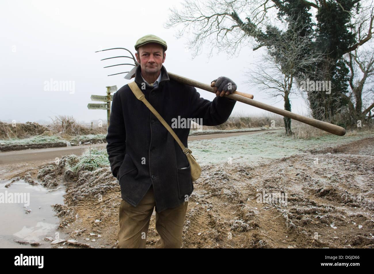 Portrait of mature farmer holding pitchfork - Stock Image