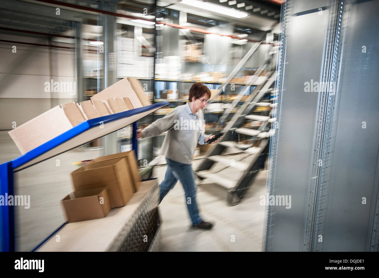 Female warehouse worker moving trolley cart - Stock Image