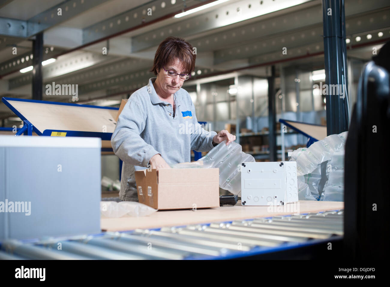 Female warehouse worker packing box for conveyor belt - Stock Image