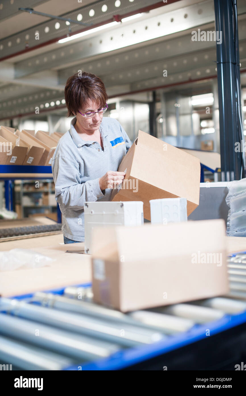 Female warehouse worker labeling box for conveyor belt - Stock Image