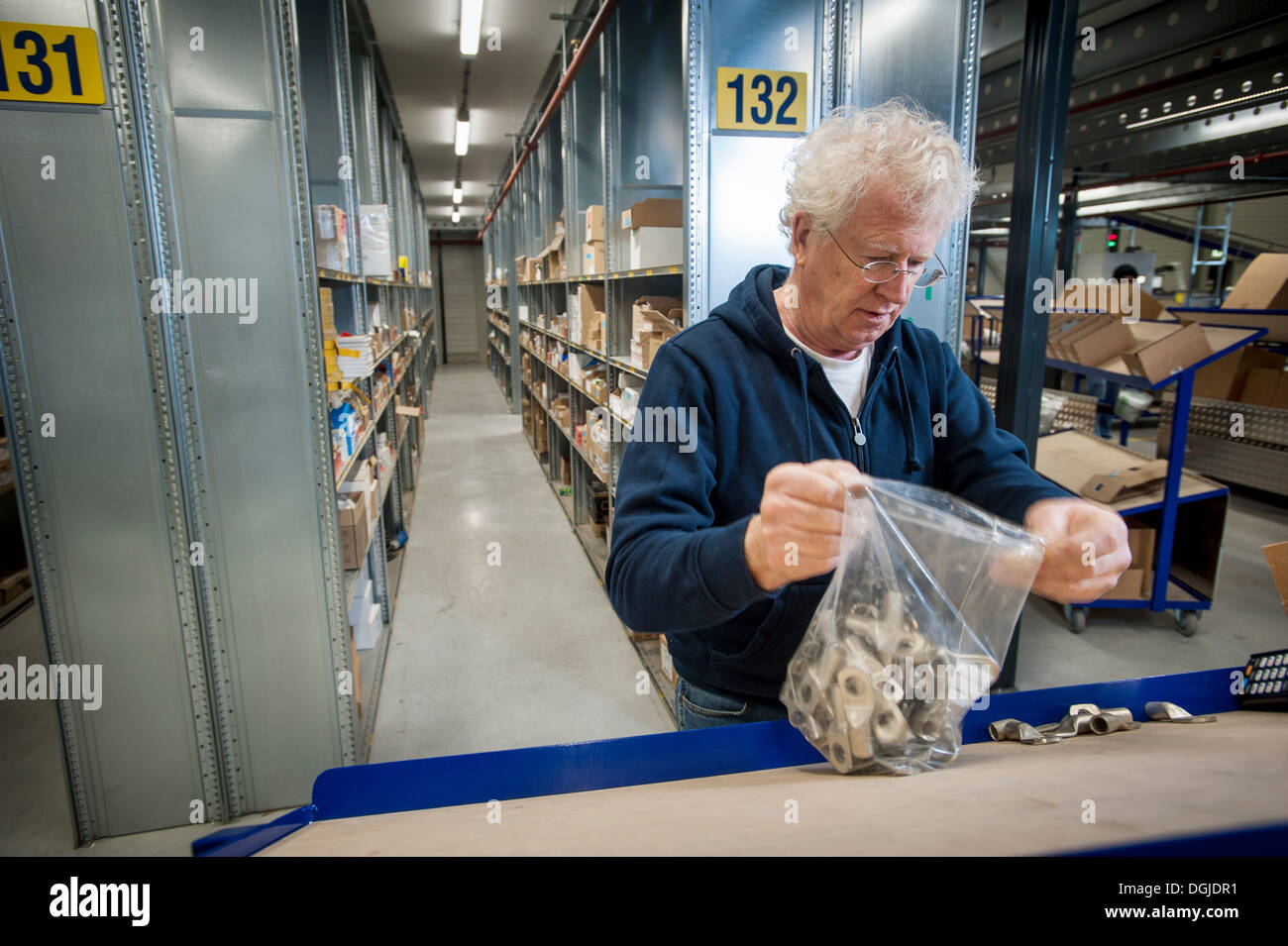 Male warehouse worker selecting item from conveyor belt - Stock Image