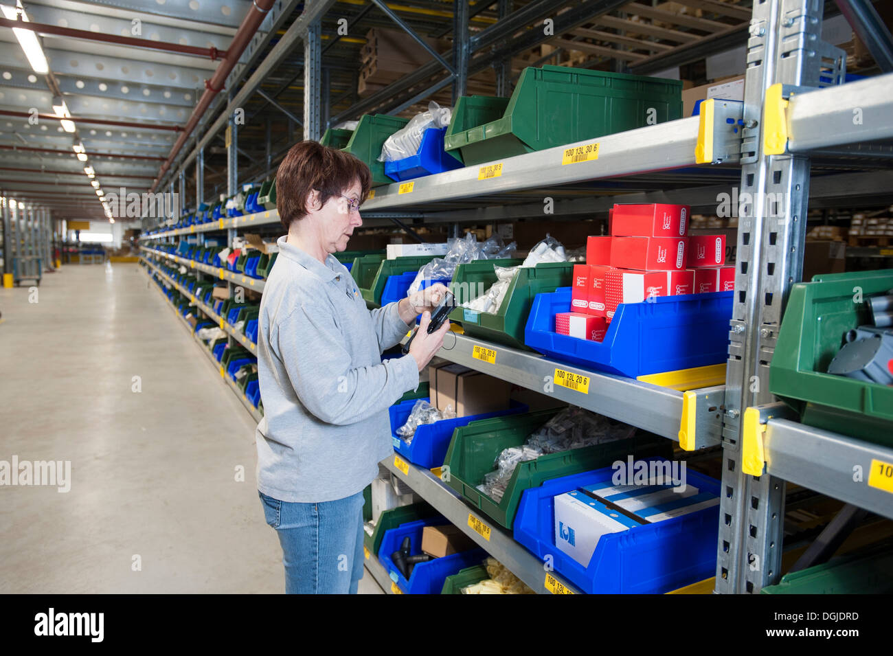 Female warehouse worker selecting item from shelving - Stock Image