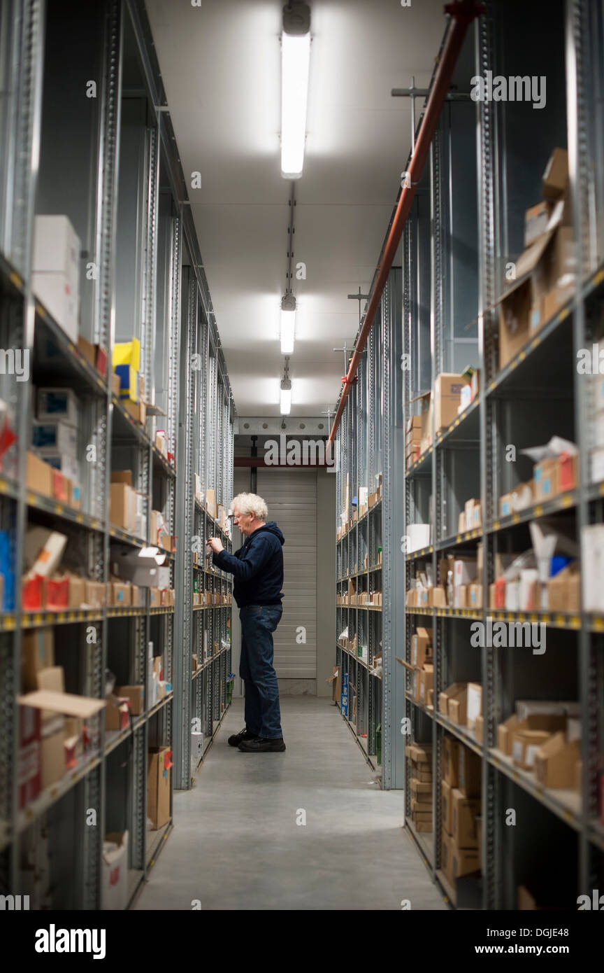 Male warehouse worker selecting item from shelving - Stock Image