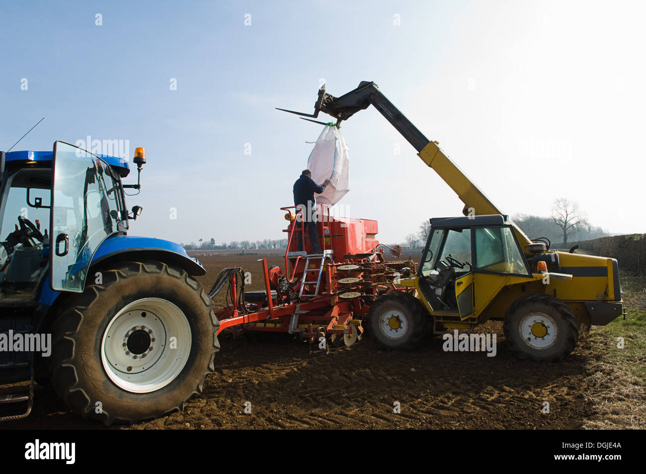 Farmer filling machinery with seed for planting - Stock Image