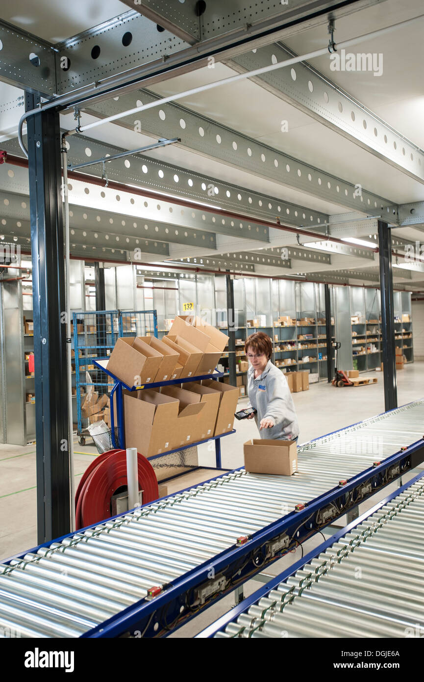 Female warehouse worker placing box onto conveyor belt - Stock Image