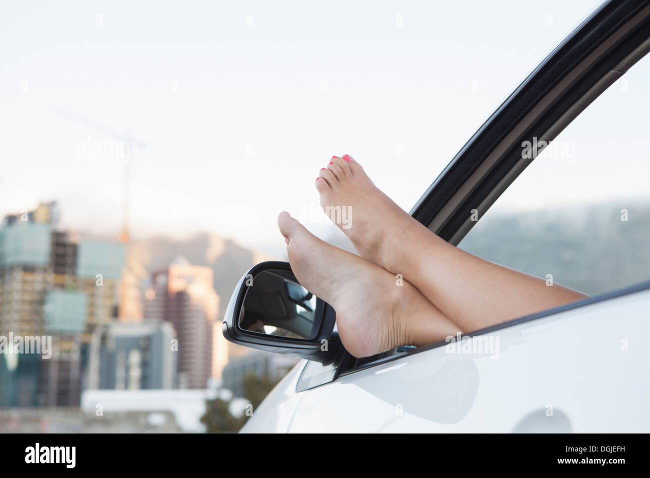 Young woman with feet up through car window - Stock Image