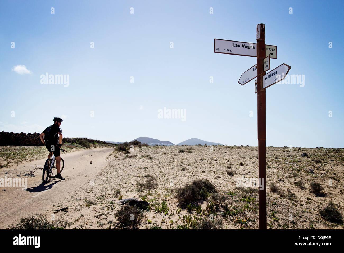 Man mountain biking past sign post, Lanzarote Stock Photo