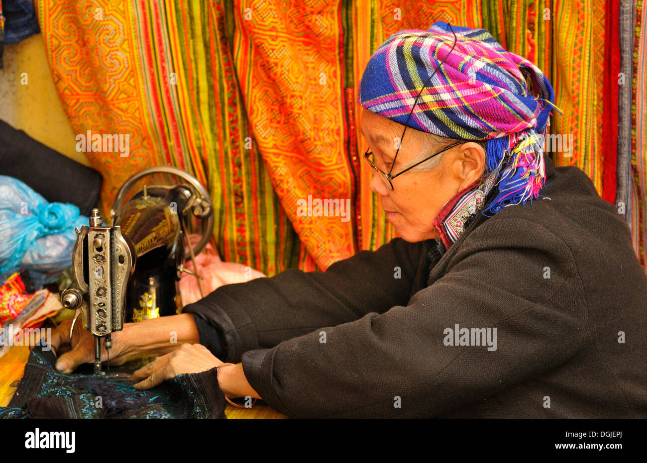 Old sewing woman of the Hmong ethnic group, old mechanical sewing machine on the market of Sapa or Sa Pa, Lao Cai province - Stock Image