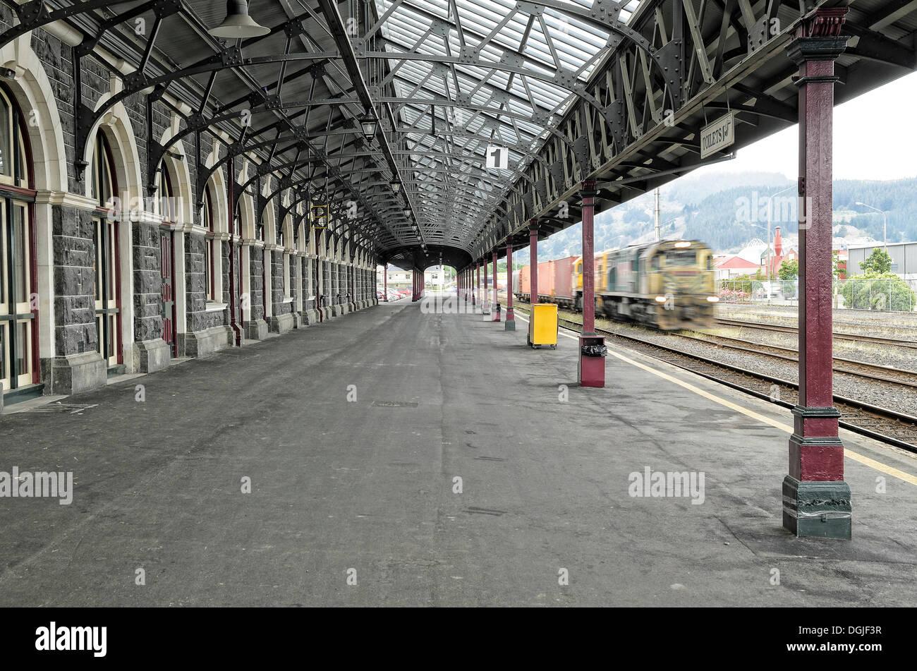 Platform with a train entering the station, historic Dunedin Railway Station, Dunedin, South Island, New Zealand, Oceania - Stock Image