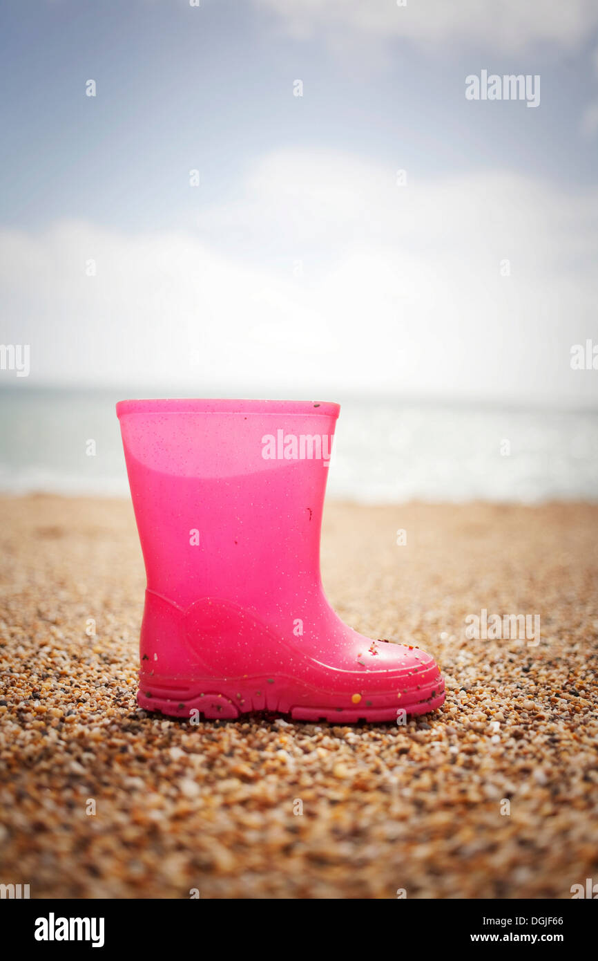 Pink rubber boot standing on sand Stock Photo