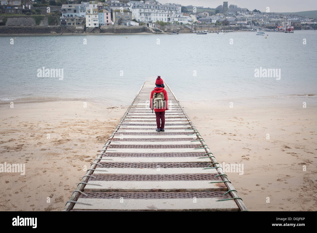 Rear view of boy standing on pier overlooking sea - Stock Image