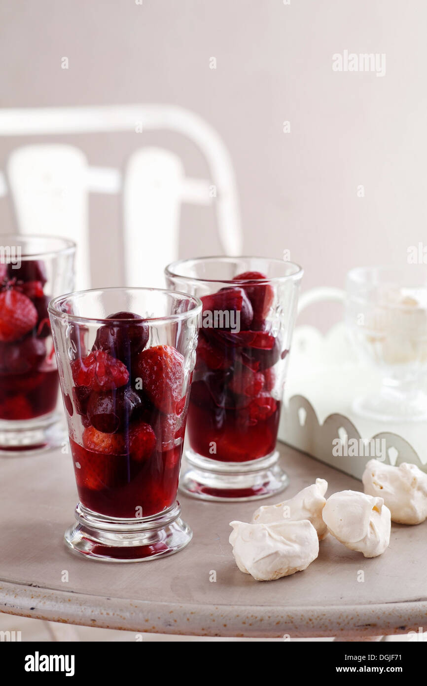Mixed berries in glasses with meringues - Stock Image