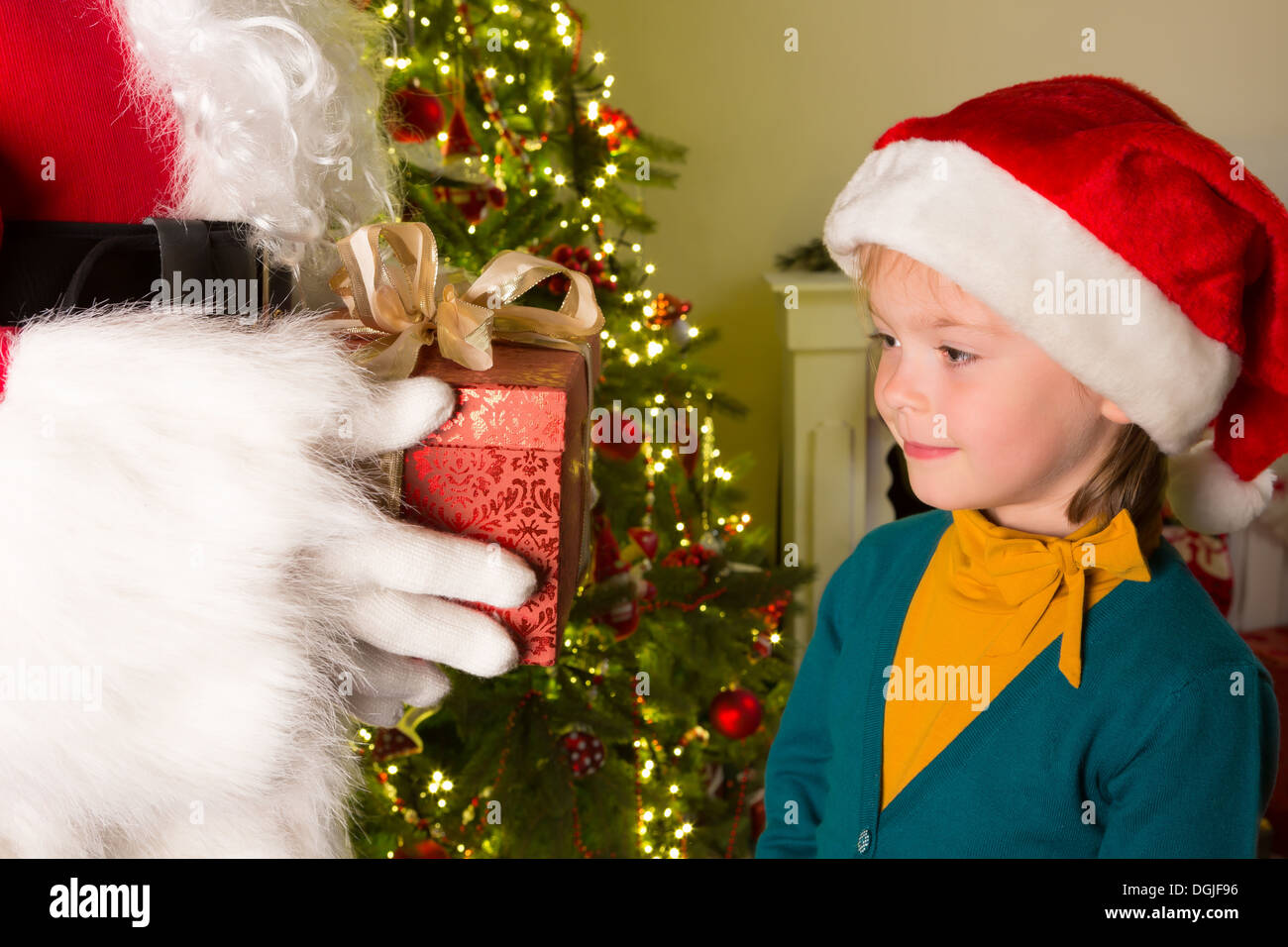 little 5 year old girl getting a red gift from santa claus