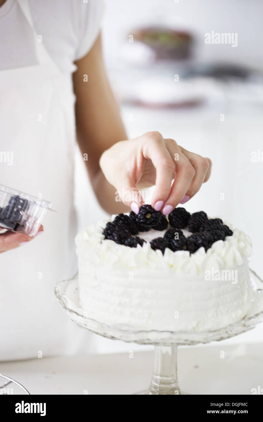 Woman decorating cake with fresh blackberries - Stock Image