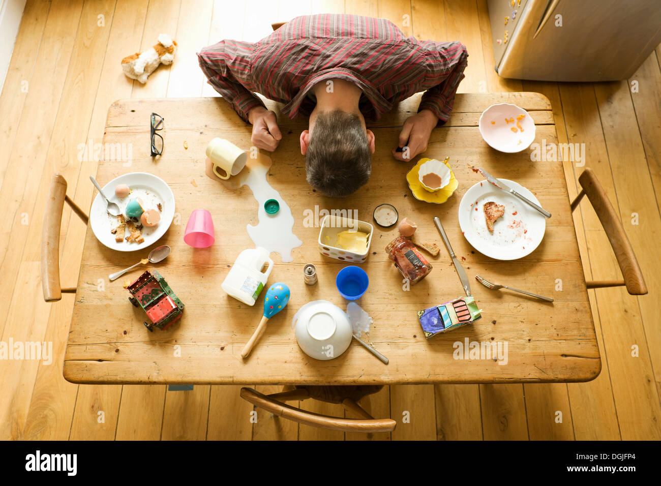 Overhead view of breakfast table with mature man amongst messy plates - Stock Image