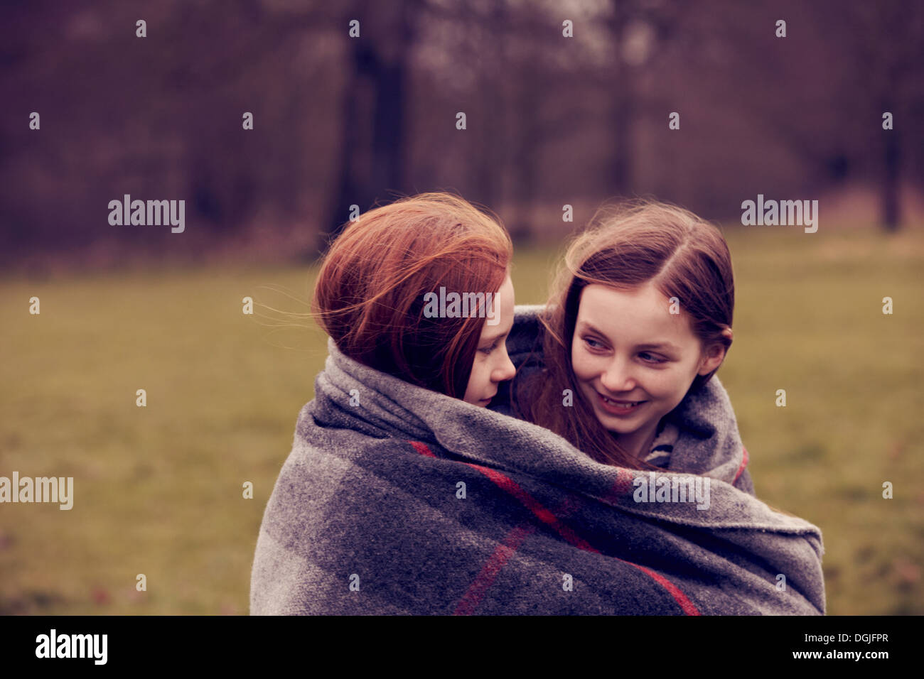 Girls wrapped in a blanket outdoors, smiling - Stock Image